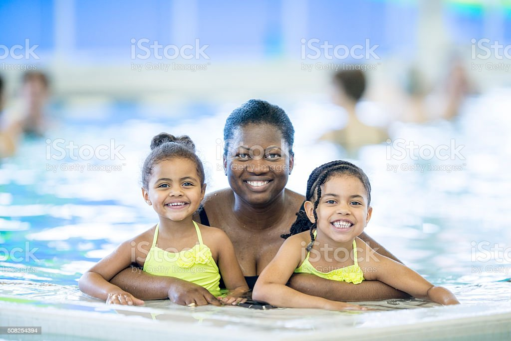 Mother with Her Daughters at the Pool stock photo