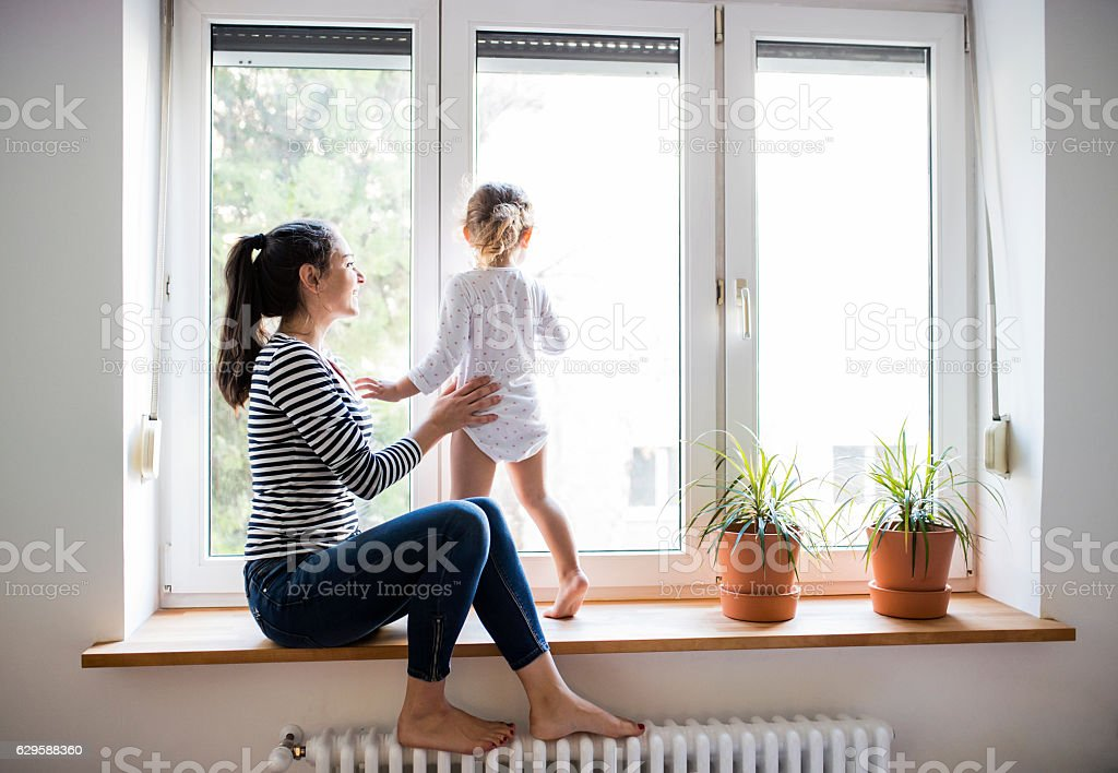 Mother with her little daughter looking out of window stock photo