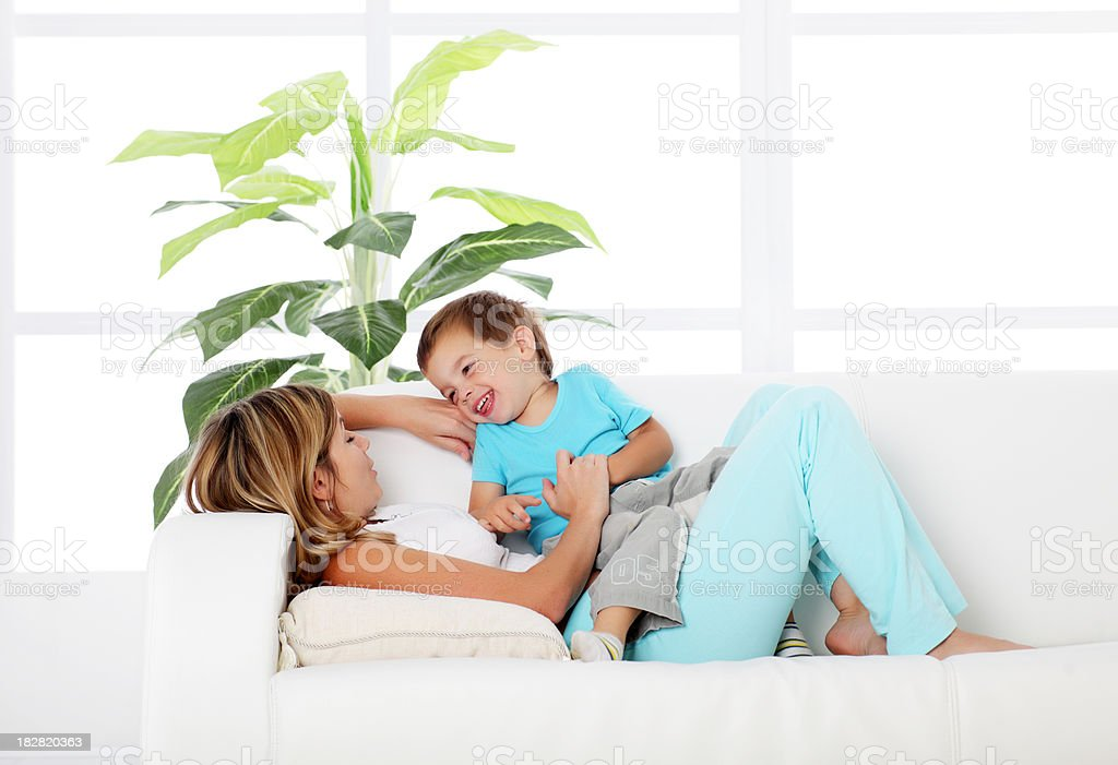 Mother with her little son playing on sofa. royalty-free stock photo