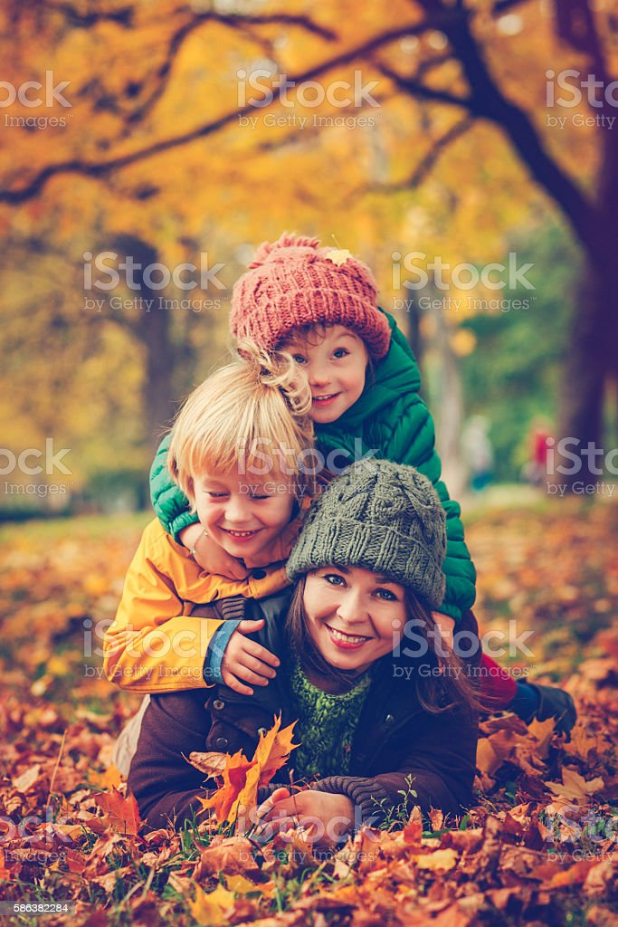 Mother with her son and daughter in autumn park stock photo