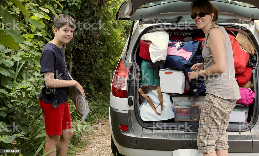 mother with her son loads the luggage in the trunk stock photo