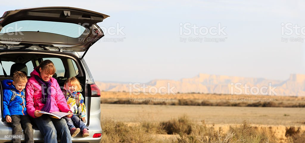 mother with kids looking at map while travel by car stock photo