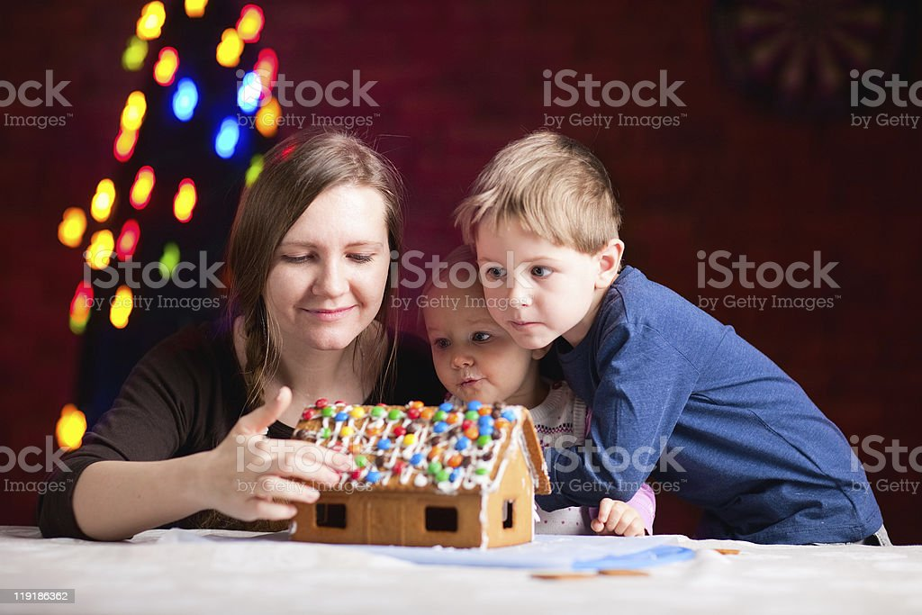 Mother with kids making gingerbread house stock photo