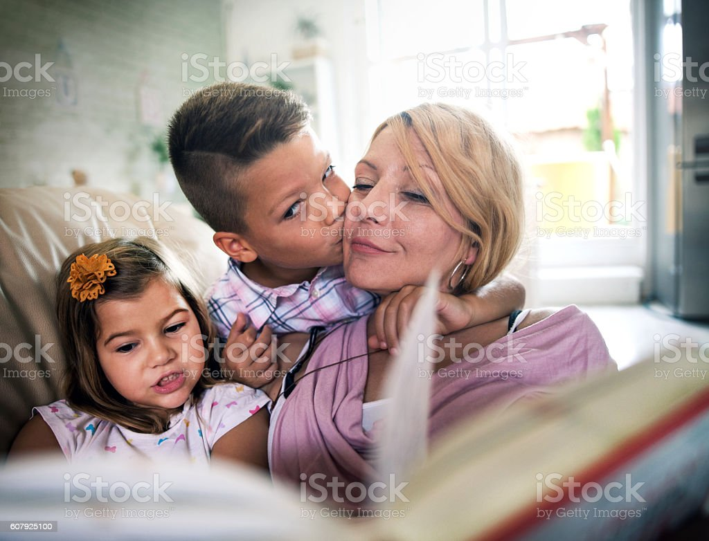 mother with kids  reading a book at home stock photo