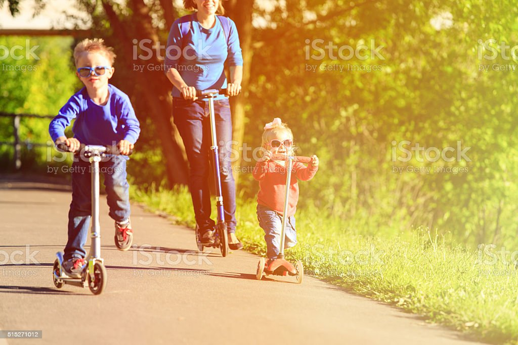 mother with kids riding scooters in summer stock photo