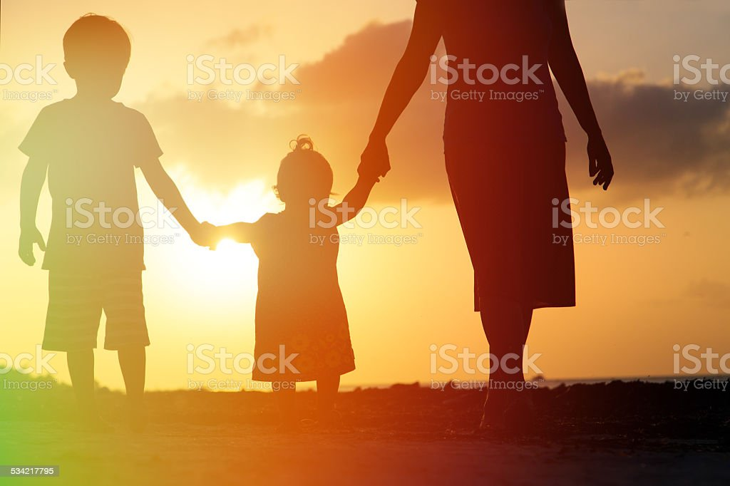 mother with kids walking on beach at sunset stock photo