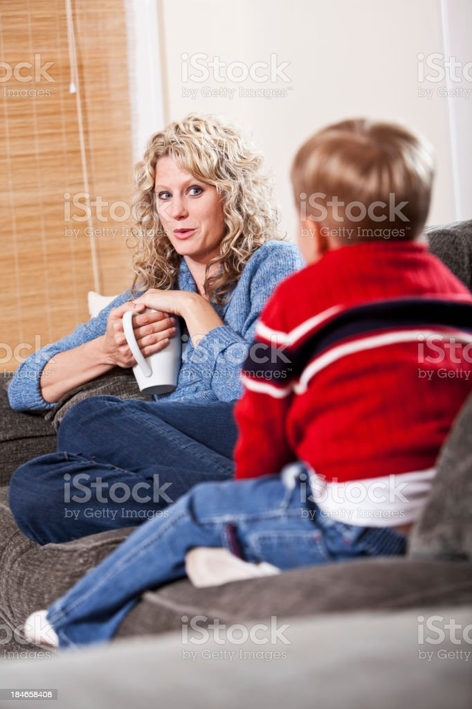 Mother with little boy on sofa stock photo