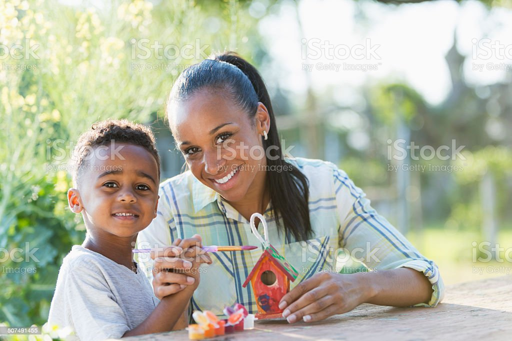 Mother with little boy painting bird house stock photo