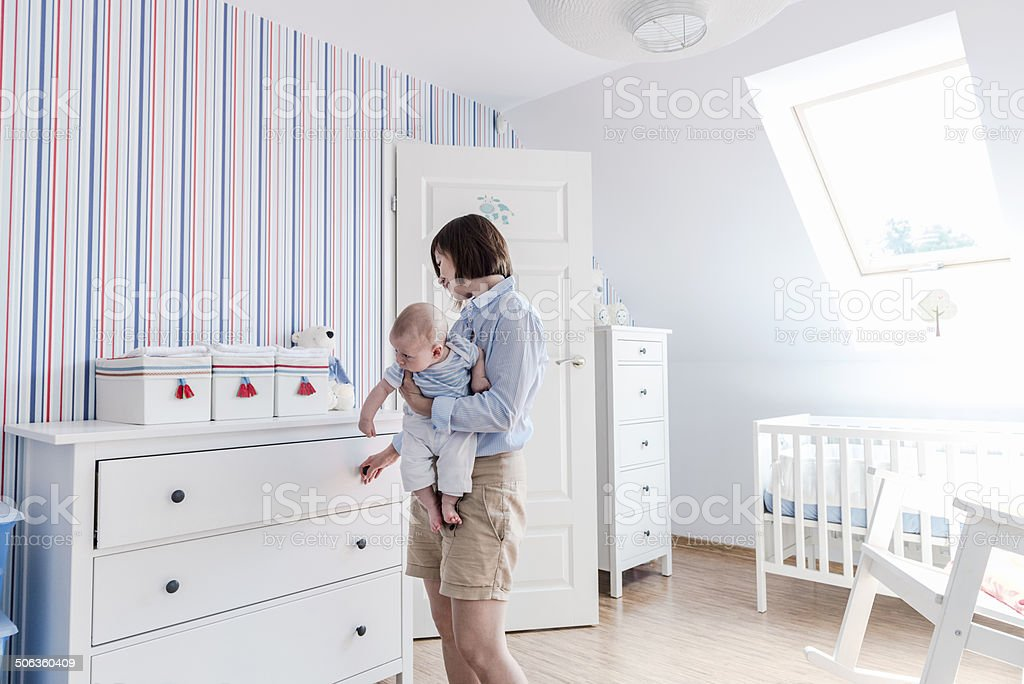 Mother with little child on hands, baby's room, white furnitures stock photo