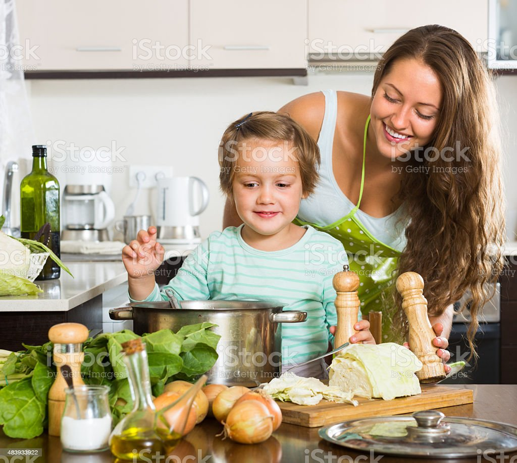 Mother with little daughter cooking at home stock photo