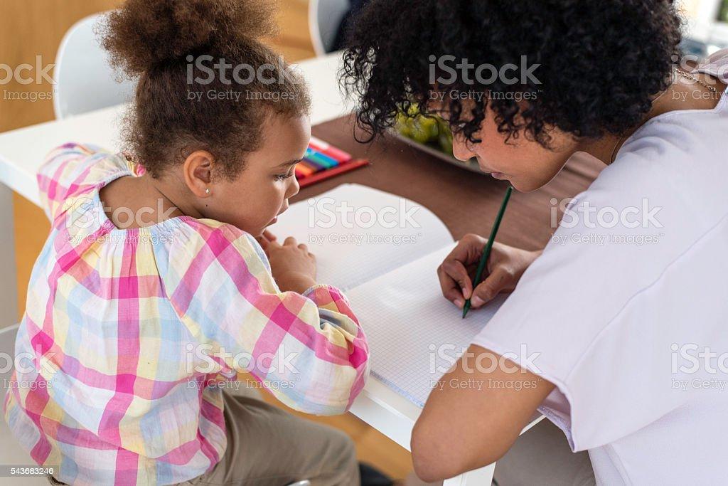 Mother with little girl doing homework stock photo