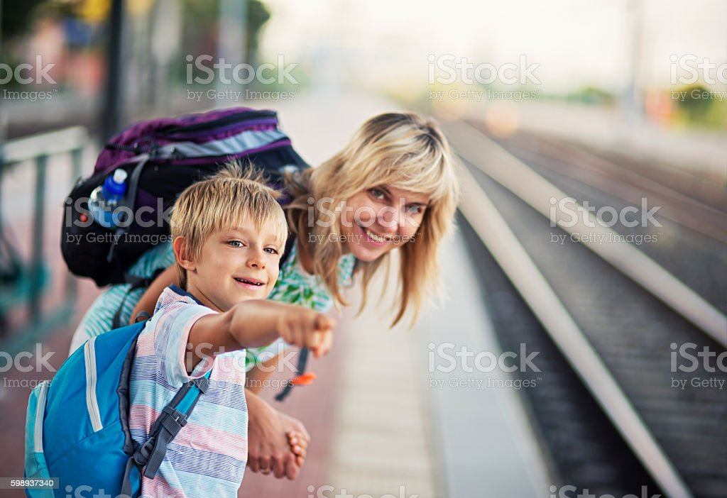 Mother with son on train station watching the incoming train stock photo