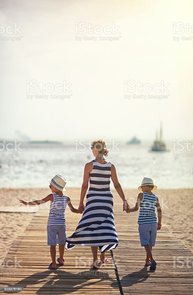 Mother with sons walking to the beach stock photo