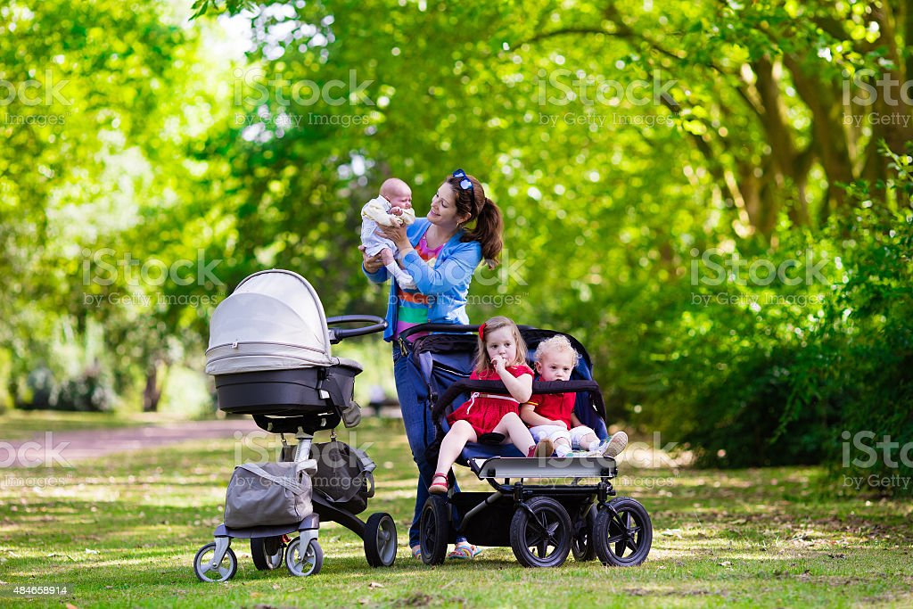 Mother with three children in buggy and stroller stock photo