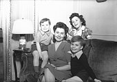 Mother with three children (4-5, 6-7, 8-9) posing in living room, (B&W), portrait