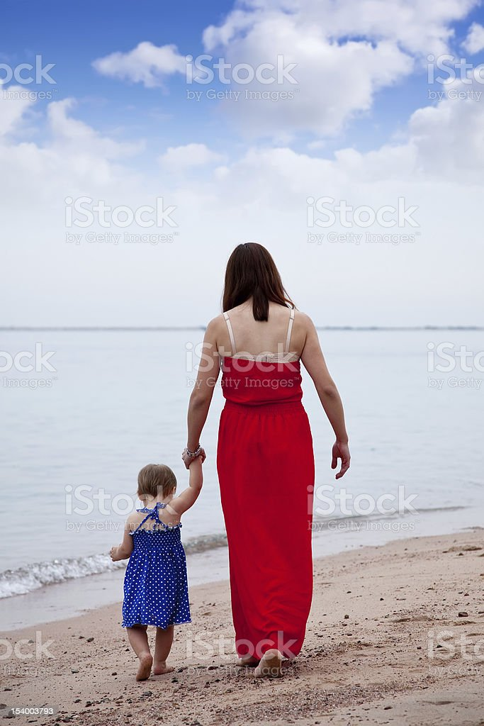 mother with  toddler walking  on sand beach royalty-free stock photo