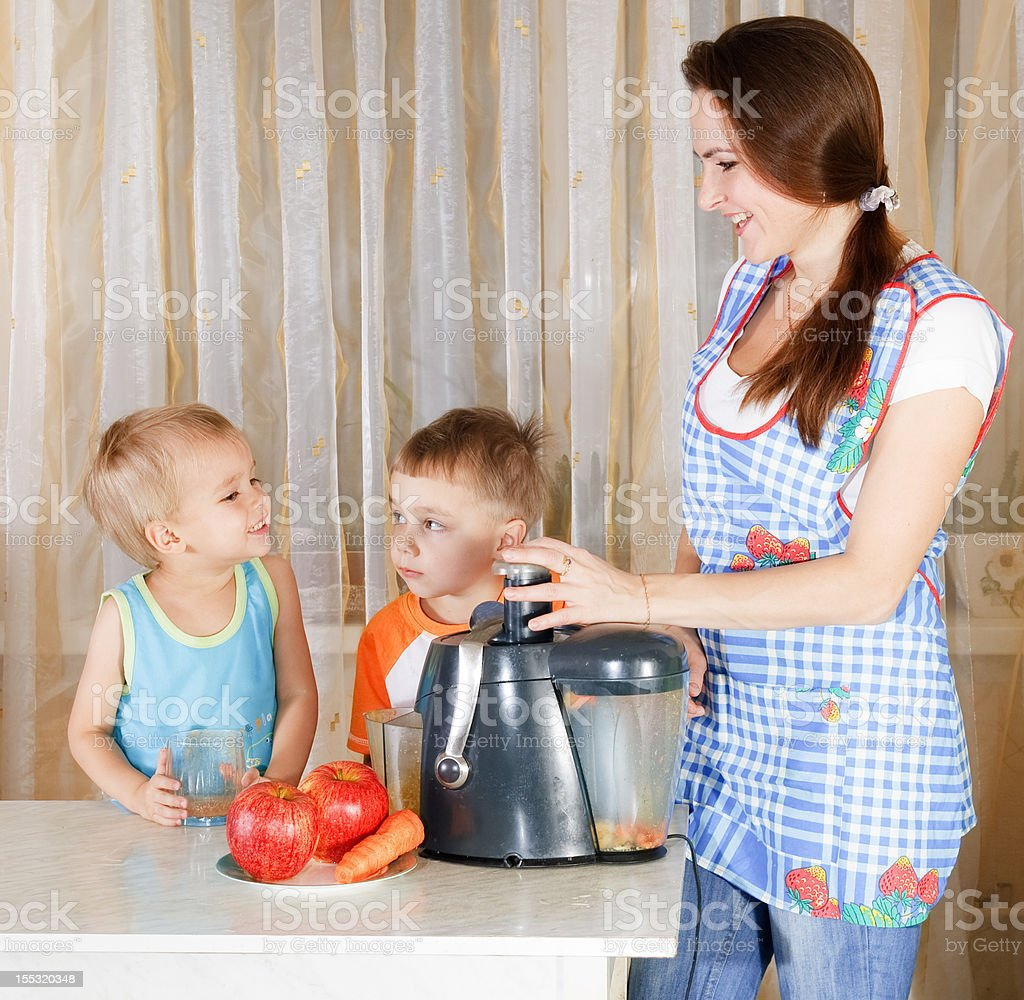 Mother with two kids doing juice royalty-free stock photo