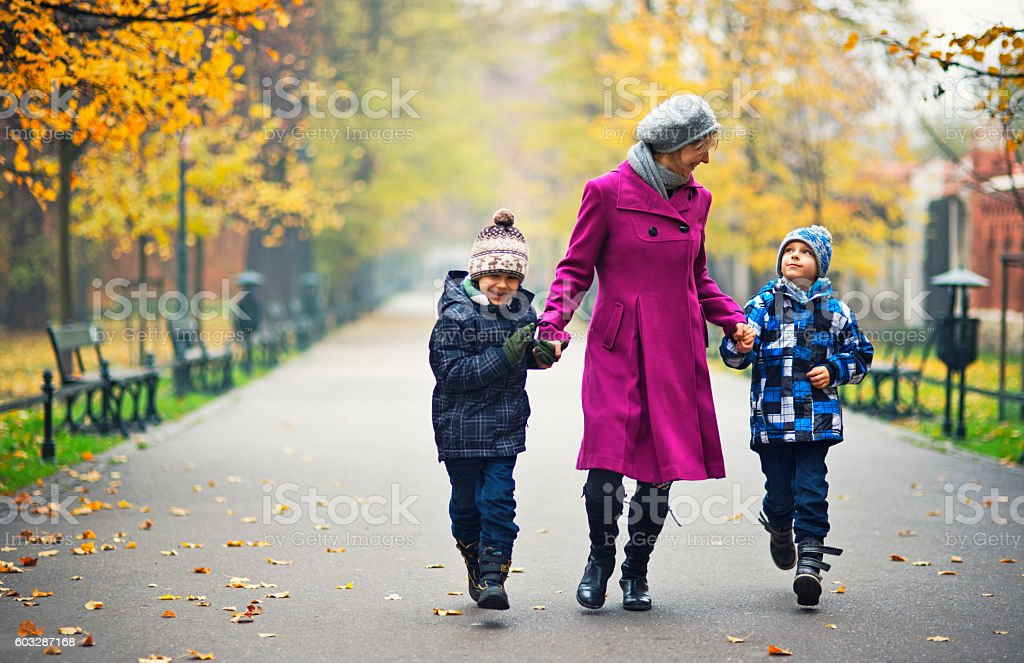 Mother with two sons walking in autumn park. stock photo