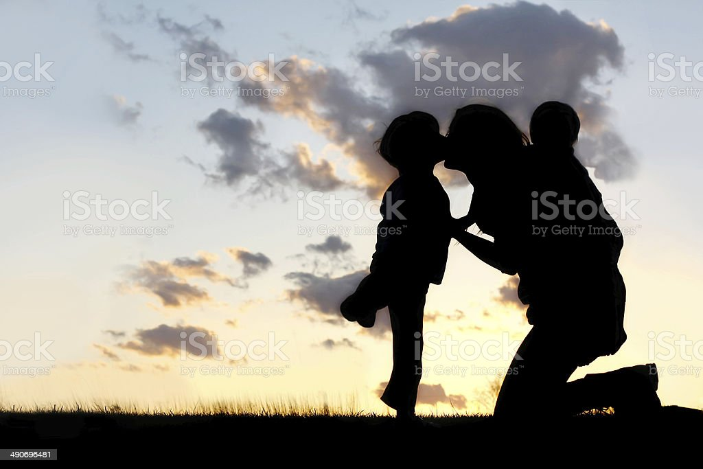 Mother with Two Young Children Hugging and Kissing stock photo
