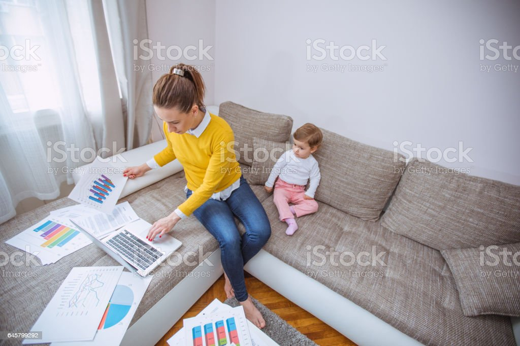 Mother working and taking care of the baby stock photo