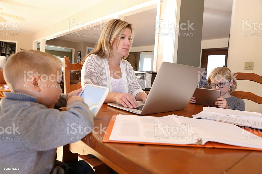 Mother Working From Home With Her Chidren Next To Her stock photo