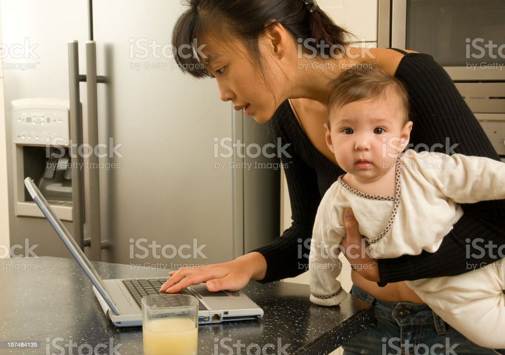 mother working on computer with bored baby stock photo