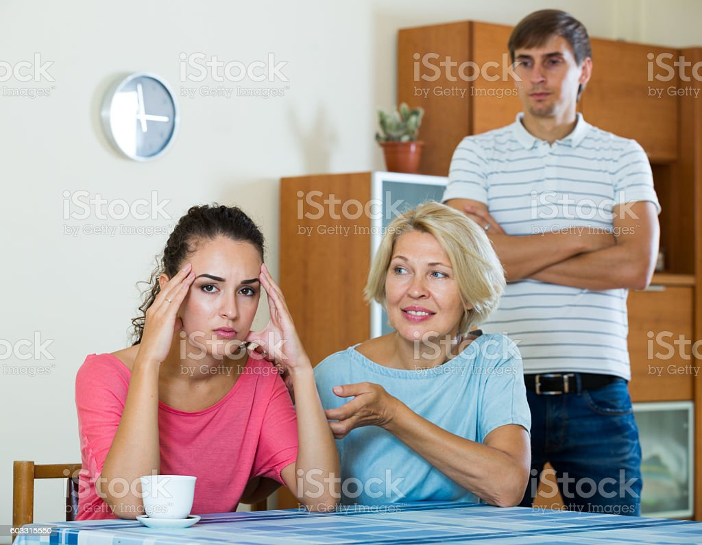 Mother-in-low comforting girl after quarrel with husband stock photo