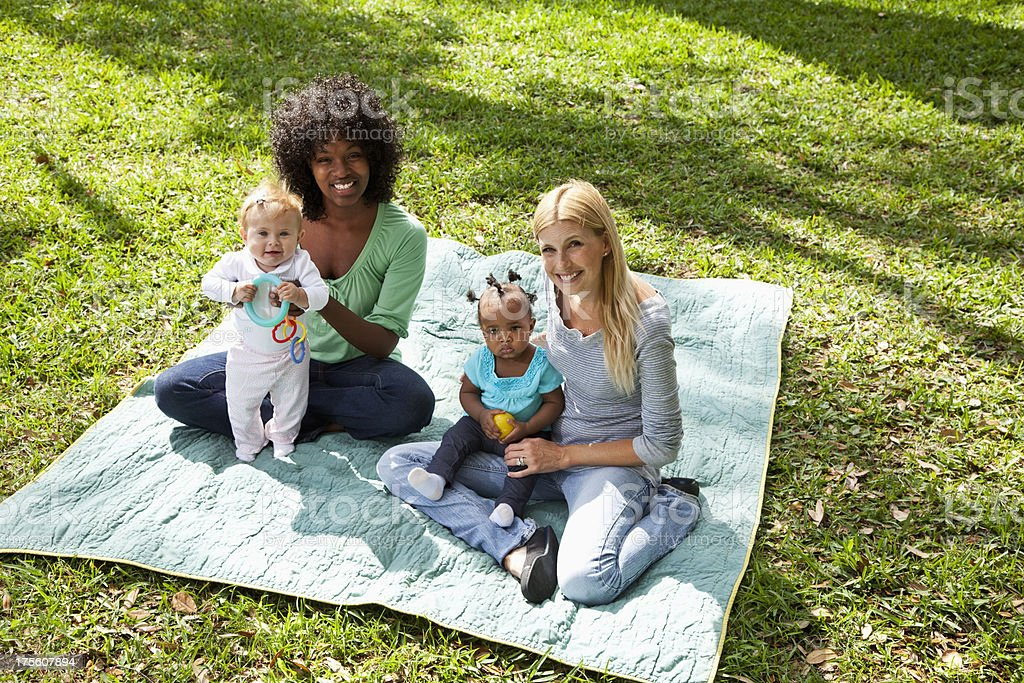 Mothers and babies on picnic blanket stock photo