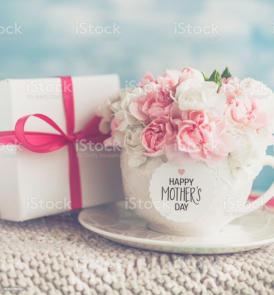 Mother's Day gift and cup filled with fresh carnation bouquet stock photo