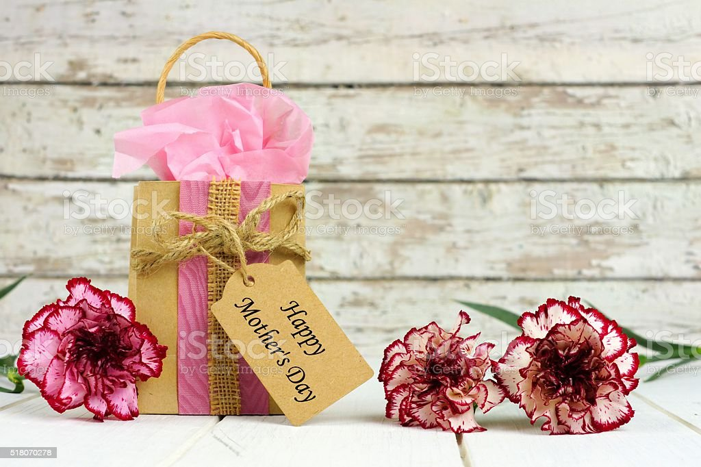 Mothers Day gift bag, tag and flowers against white wood stock photo