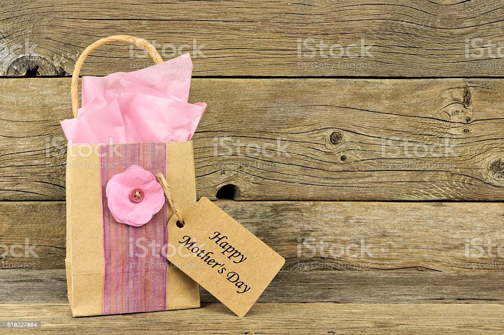 Mothers Day gift bag with tag against rustic wood stock photo