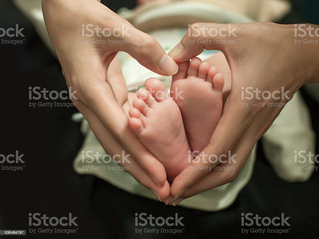 Mother's hand and baby's foot stock photo