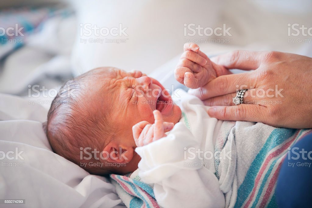 Mother's Hand Holding Comforting Crying Baby stock photo