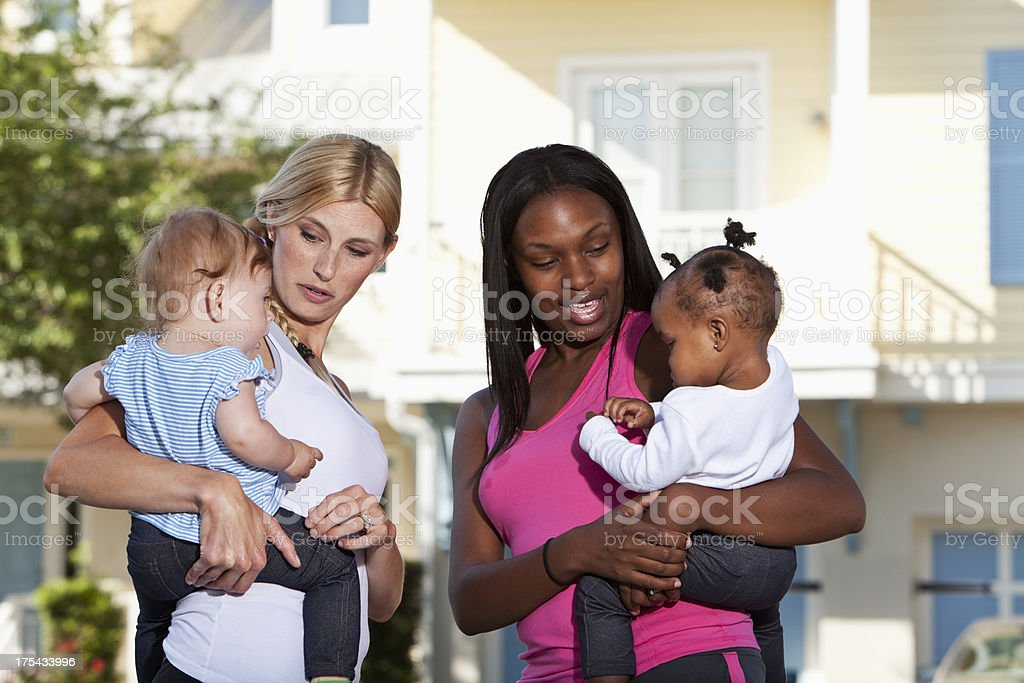 Mothers holding baby girls stock photo