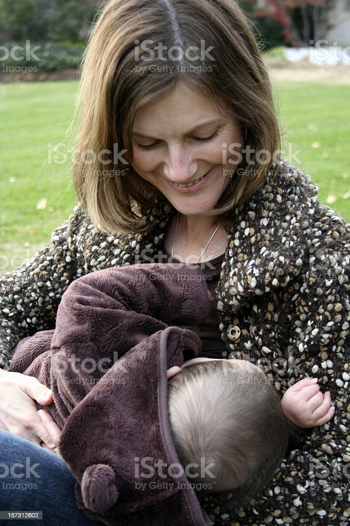 Mother's Milk: breastfeeding a baby in a soft bear coat royalty-free stock photo