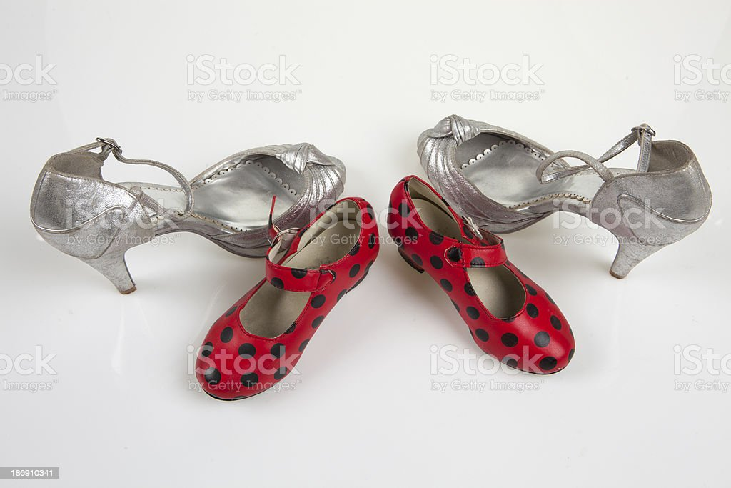 Mother's silver high-heeled  and  daughter's  dots shoes royalty-free stock photo