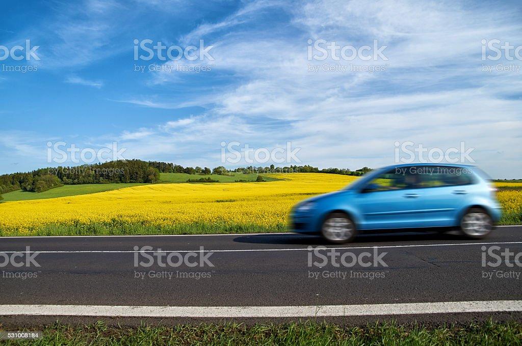 Motion blur blue passenger car speeding on the asphalt road stock photo