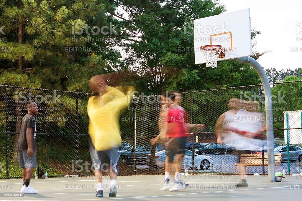 Motion Blur Man Shooting Basketball In Pickup Game At Park stock photo