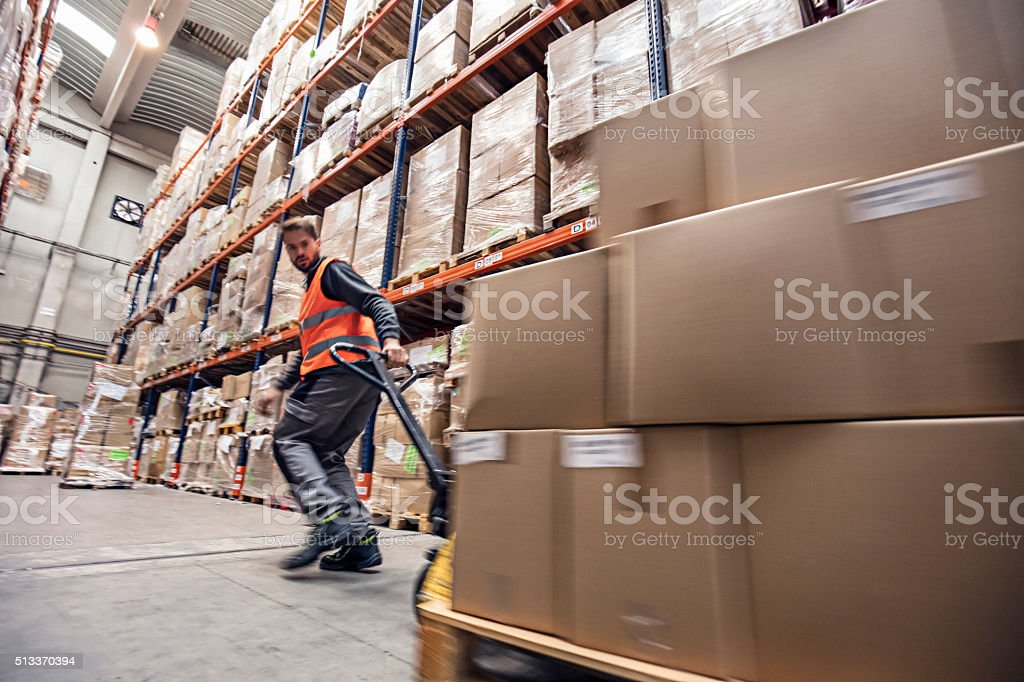 Motion blur of a man moving boxes in a warehouse stock photo