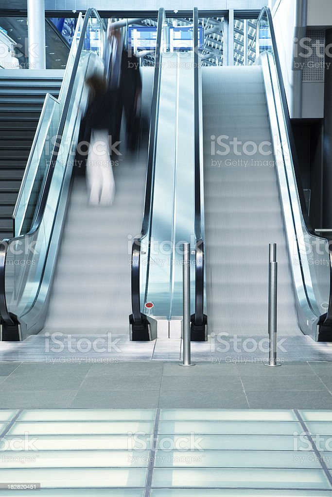 Motion Blur of Businesspeople with Luggage on Escalator in Airport royalty-free stock photo