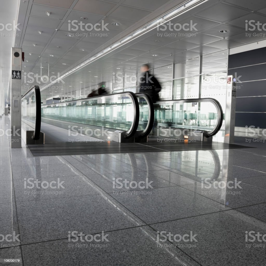 Motion Blur of People Walking on Moving Sidewalk at Airport stock photo