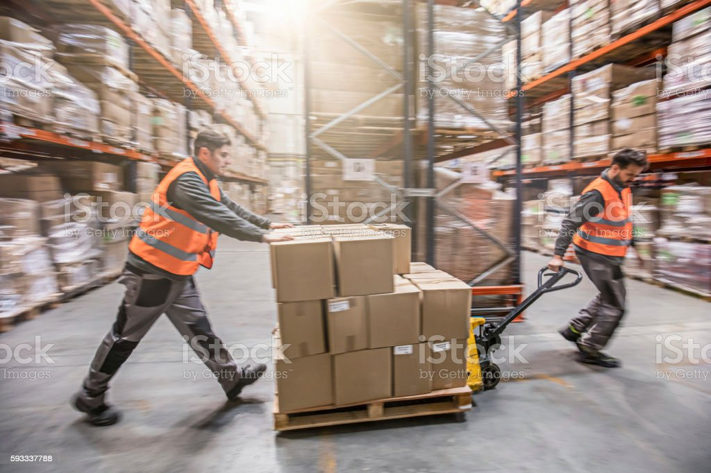 Motion blur of two men moving boxes in a warehouse stock photo