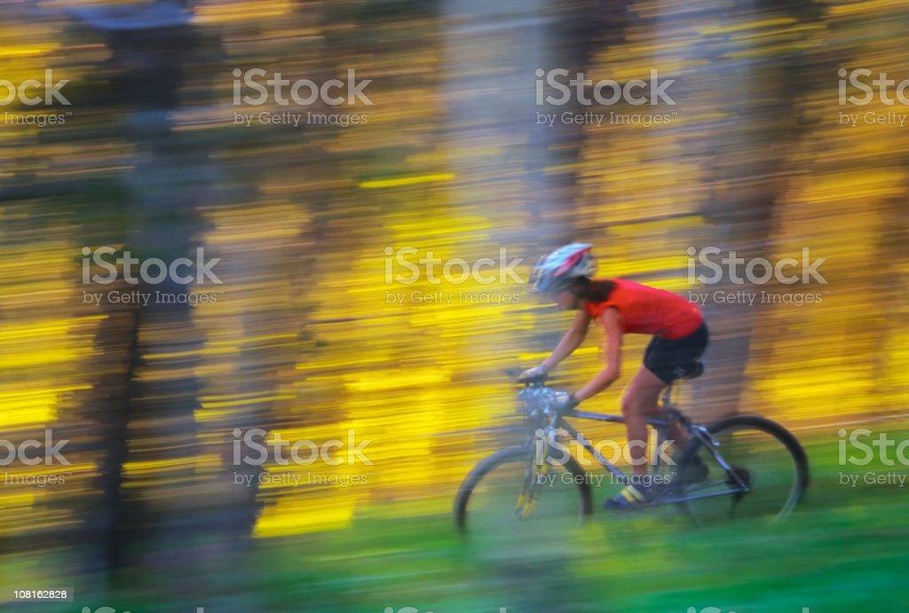 Motion Blur of Woman Mountain Biking Down Trail royalty-free stock photo