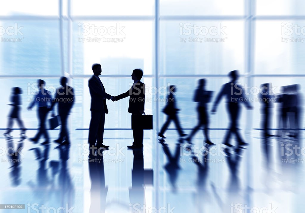Motion blur sihouette of businessmen shaking hands royalty-free stock photo