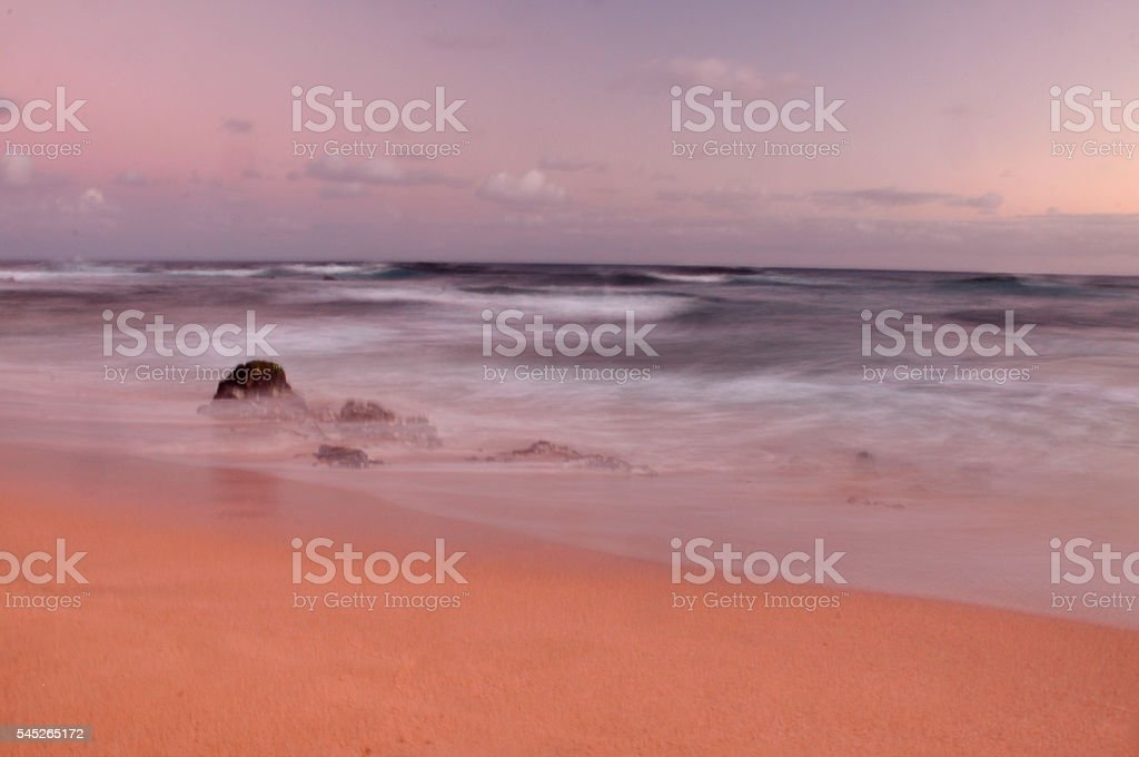 motion blur waves and rocks on beach at sunset stock photo