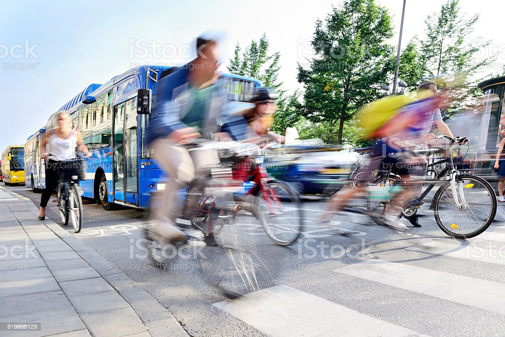 Motion blurred bicyclists in traffic stock photo