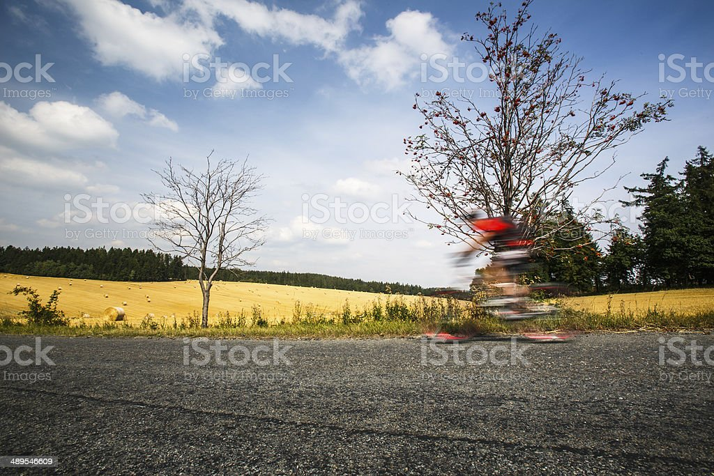 Motion blurred biker on a road stock photo