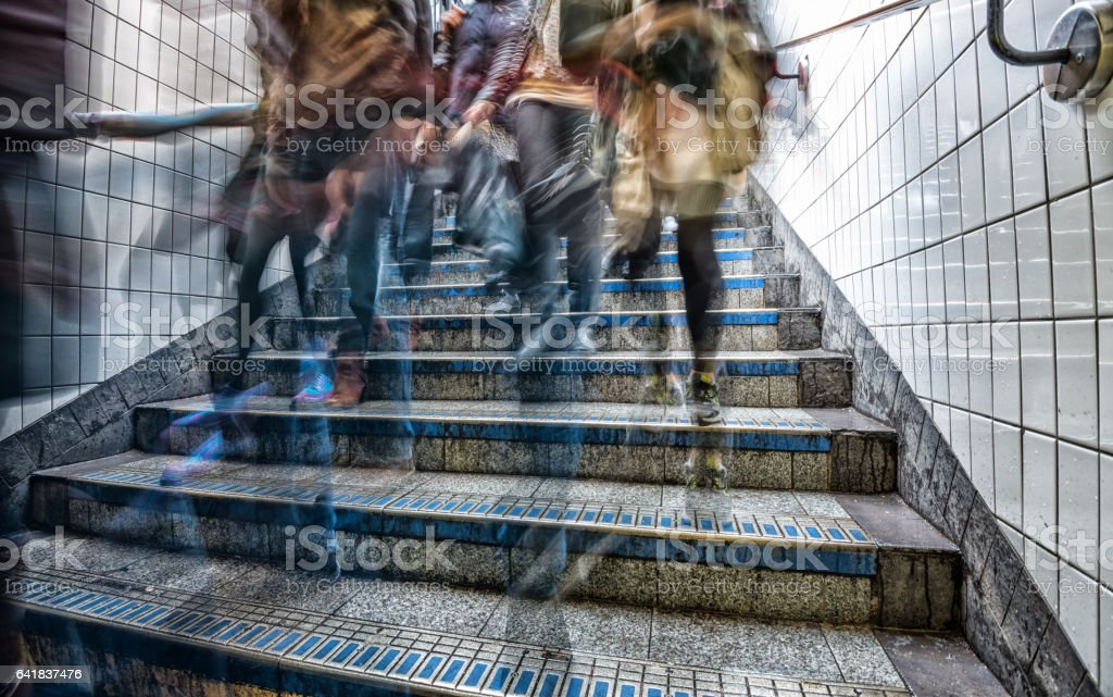 Motion blurred commuter in subway station stairs stock photo