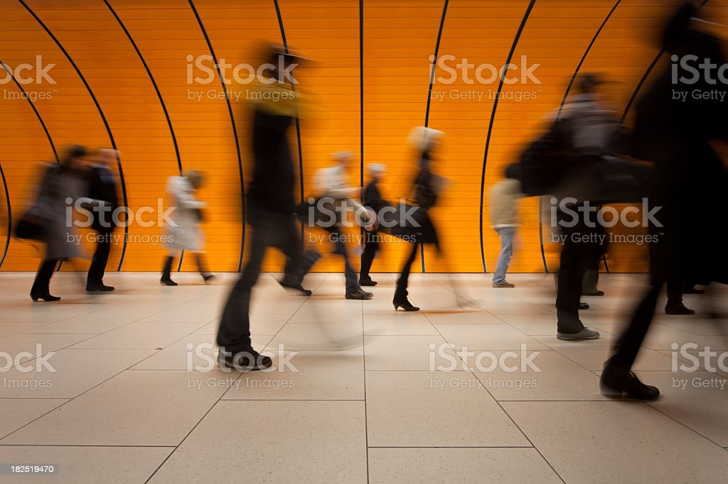 Motion blurred commuters against a modern orange background stock photo