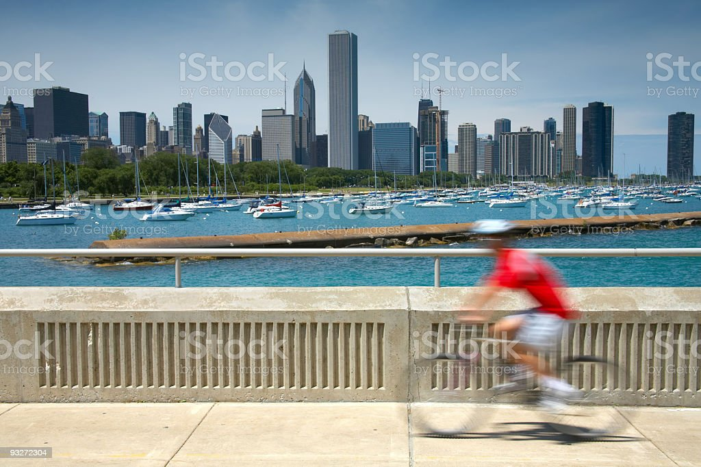 Motion blurred cyclist across the waters and Chicago skyline stock photo